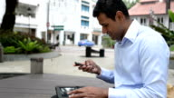 Cheerful Indian Businessman Multi-tasking with Digital Tablet and Phone video