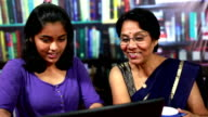 Cheerful Indian Senior Woman and Teenager Girl Using Laptop video