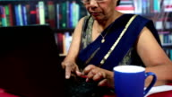 Cheerful Indian Senior Woman Using Laptop in a Library video