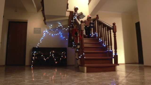 Cheerful kids carrying presents downstairs. video