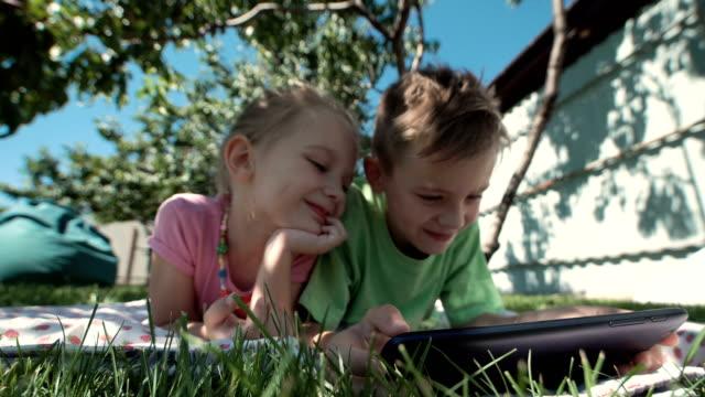 Cheerful kids watching tablet in garden video