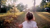 A cheerful little girl running up on a hill in the nature on a sunny summer day. Slow mo, back view video