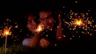 Cheerful loving girl and man laying on the grass with burning sparklers at night. Super slow motion video shot at 500 fps video