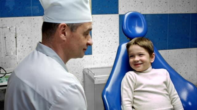 Cheerful man dentist talking to little boy video