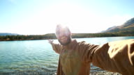 Cheerful man in nature takes selfie portrait near lake video