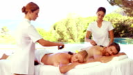 Cheerful masseurs doing hot stone massage to a relaxed couple video