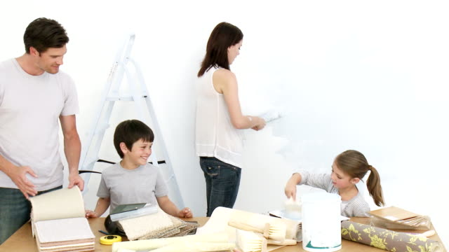 Cheerful parents and their children painting a room video