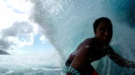 SLOW MOTION: Cheerful pro surfer surfing big tube barrel wave video