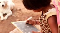 Cheerful Rural Indian girl writing learning ABC video