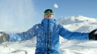 PORTRAIT: Cheerful snowboarder playing with snow in mountain ski resort video