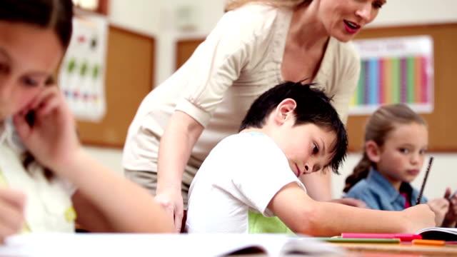 Cheerful teacher helping a pupil video