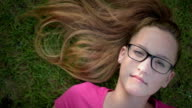 Cheerful teenage girl lying on the grass and looking at the sky, shoot from above video