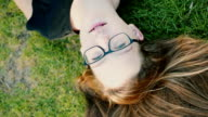 Cheerful teenage girl lying on the grass and looking at the sky, shoot from above, slow motion video