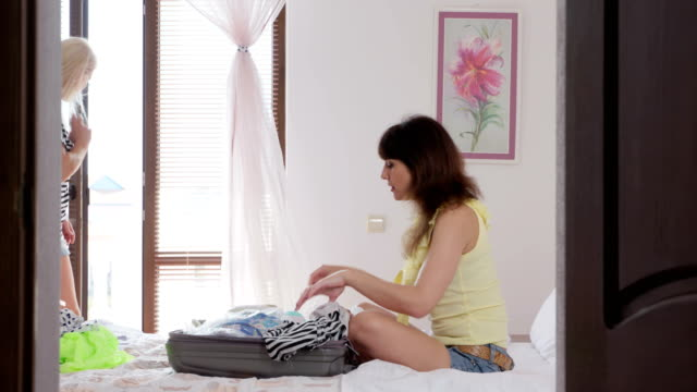 Cheerful two women arrived at hotel room unpacking travel bag on bed video