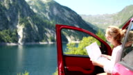 Cheerful woman exploring nature by car using map video