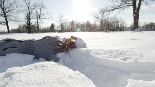 SLOW MOTION: Cheerful woman lies down and makes snow angel video