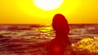 SLOW MOTION: Cheerful woman splashing and playing in the sea video