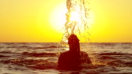 SLOW MOTION: Cheerful woman tossing hair back in the sea video