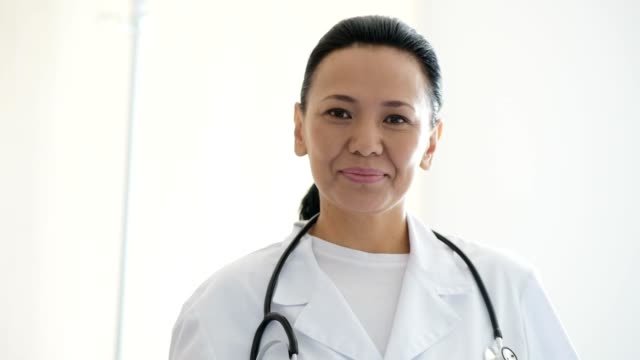 Cheerful woman with stethoscope on the neck working in the clinic video