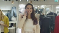 Cheerful young brunette girl is walking though a clothing store while talking on the phone. video