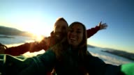 Cheerful young couple on mountain top take selfie video