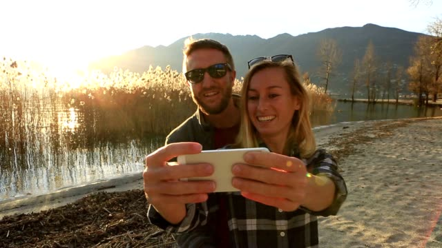 Cheerful young couple taking selfie portrait by the lake video