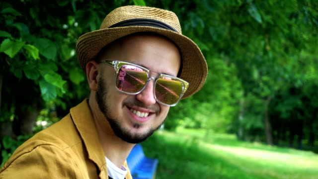 Cheerful young man in hat and sunglasses smiling on camera video