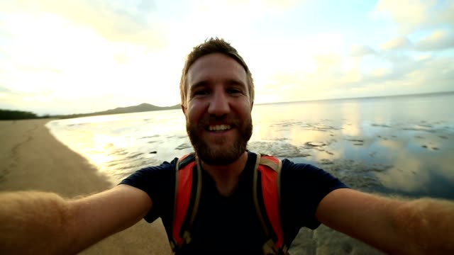 Cheerful young man on the beach takes a selfie portrait video