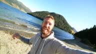 Cheerful young man takes a selfie portrait by the lake video
