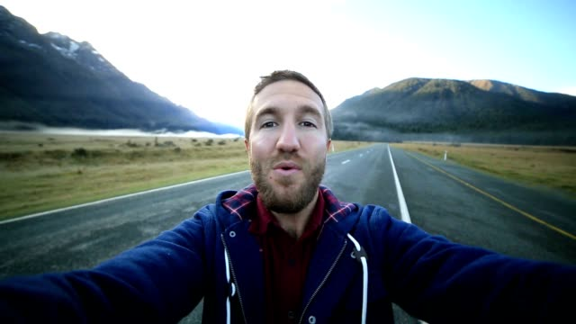 Cheerful young man takes a selfie portrait by the road video
