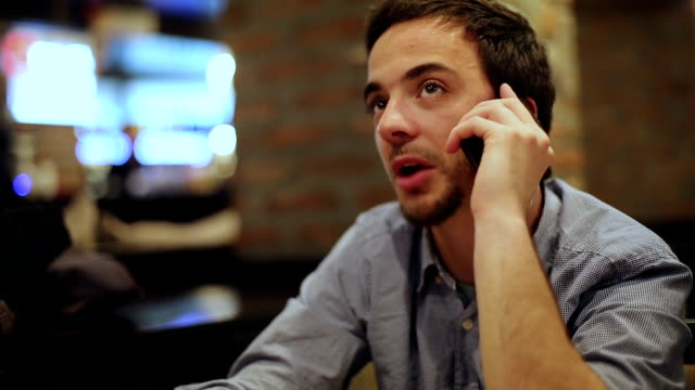Cheerful young man using smartphone in coffee shop video