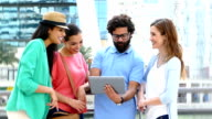 Cheerful young people in the city with digital tablet. video