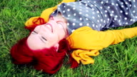 Cheerful young red haired woman relaxing in grassy meadow video