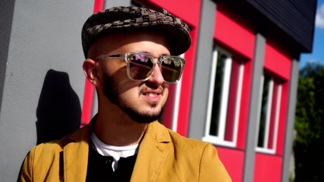 cheerful young stylish man in hat and sunglasses smiling video