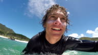 SLOW MOTION CLOSE UP: Cheerful young surfer doing duck dive video