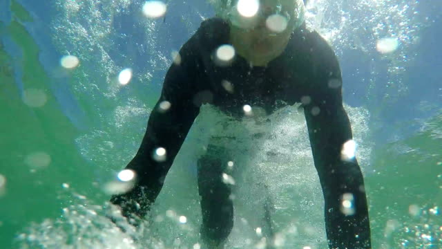SLOW MOTION CLOSE UP: Cheerful young surfer duck diving under the wave video