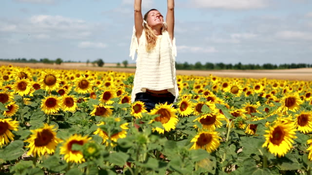 Cheerful young woman arms outstretched in middle of sunflower field video