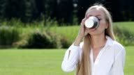 Cheerful young woman drinking coffee outside video