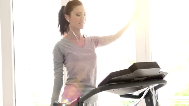 Cheerful young woman exercising on treadmill at home video