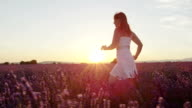 SLOW MOTION: Cheerful young woman in white dress running through beautiful purple lavender field at golden sunset in summer video