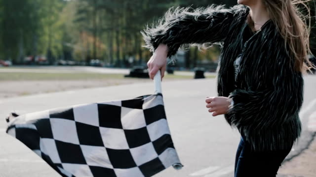 Cheerful young woman jumping and waving a race checkerd flag. Go-kart track on the background video