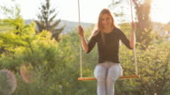 Cheerful young woman on rope swing in backyard at sunrise video