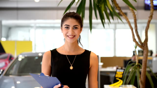Cheerful young woman posing in a car dealership video