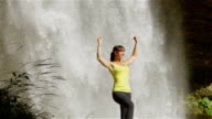 Cheerful young woman raising hands in front of the waterfall video