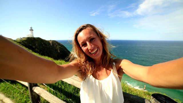 Cheerful young woman takes a selfie portrait at Cape Byron in Byron Bay, Australia. video