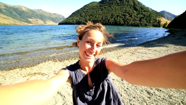 Cheerful young woman takes a selfie portrait by the lake video