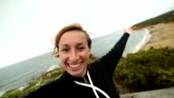 Cheerful young woman takes a selfie portrait on Bells Beach video