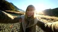 Cheerful young woman taking a selfie portrait in nature video