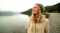 Cheerful young woman walking on lake shore-Autumn video