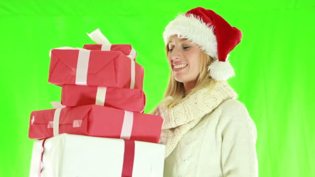 Cheerful young woman wearing christmas hat and holding presents video
